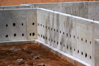 Poured foundation showing fourm ties coated with roofing cement