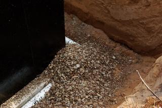 A picture of rock over a foundation drain pipe