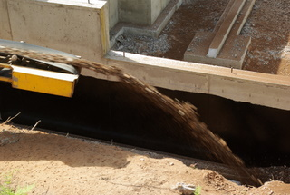 A picture of rock being put around a foundation drain