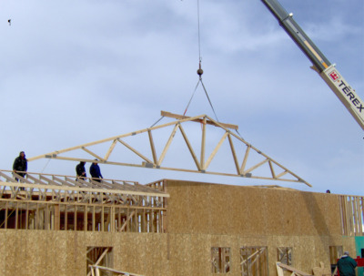 Roof trusses being installed by a crane